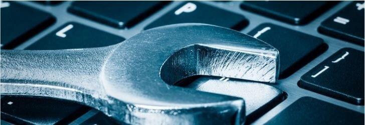Imagem utilizada para o artigo sobre manutenção preventiva da Acoplast, nesta imagem há uma chave de fendas em cima de um teclado de computador, a tonalidade da imagem é azul.