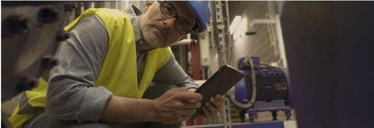 Imagem utilizada no artigo sobre contra recuo, nela há um homem agachado segurando uma prancheta, enquanto analisa uma máquina.